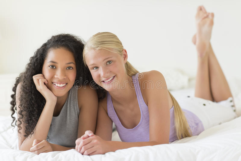 Adolescentes felices que se relajan en cama imágenes de archivo libres de regalías