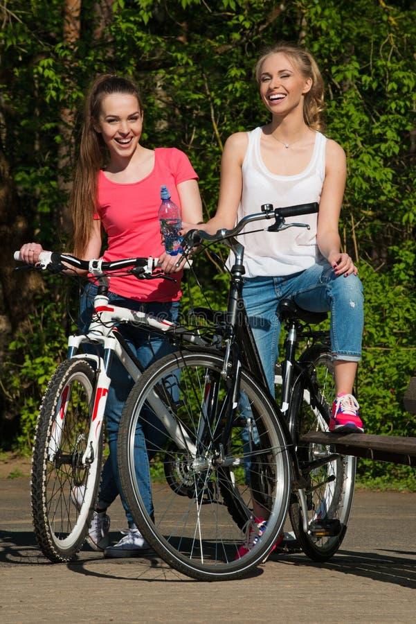 Adolescentes felizes com bicicletas imagem de stock