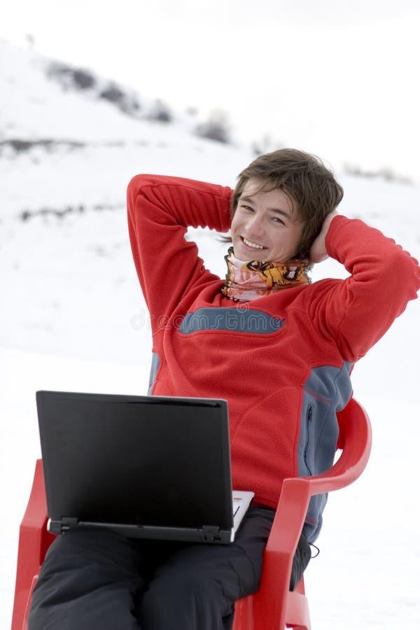 Adolescentes felizes com o portátil em montanhas do inverno foto de stock royalty free