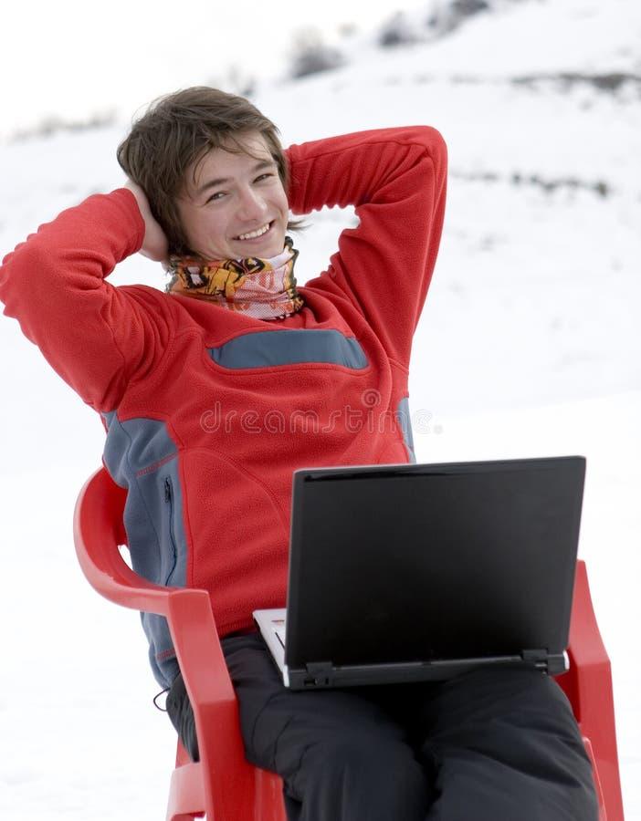 Adolescentes felizes com o portátil em montanhas do inverno fotografia de stock royalty free