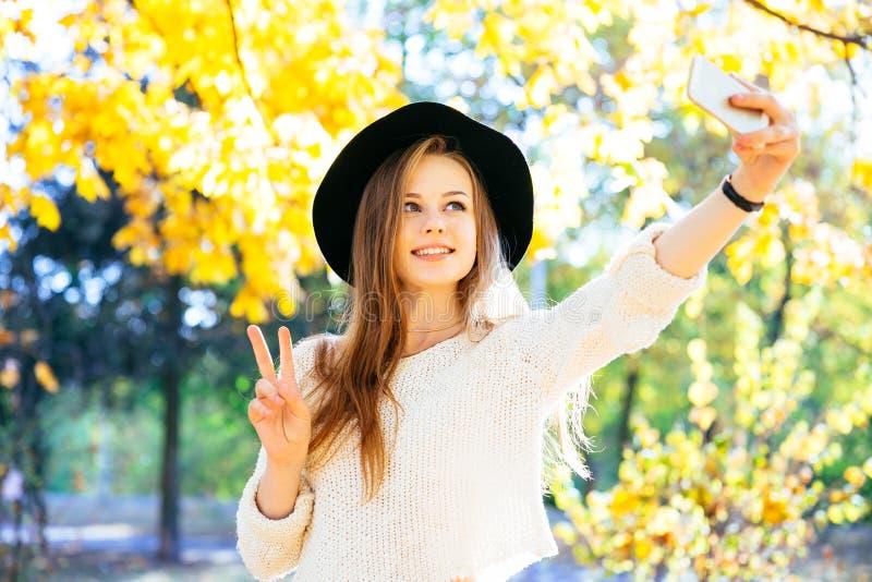 Adolescentes felizes novos que fazem o selfie e que têm o divertimento no parque do outono imagens de stock