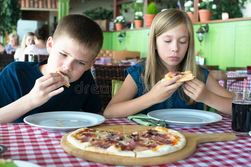 Adolescentes felizes que comem a pizza em um café Amigos ou irmãos que têm o divertimento no restaurante imagem de stock