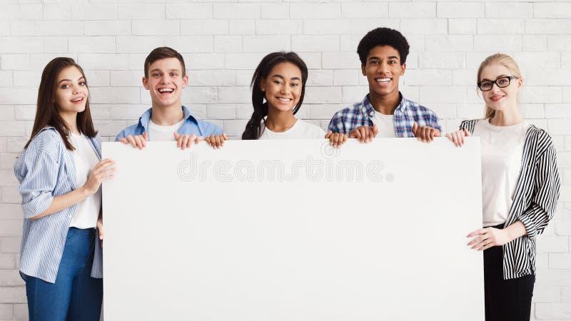 Adolescentes felizes que guardam a bandeira vazia, parede de tijolo branca imagem de stock royalty free