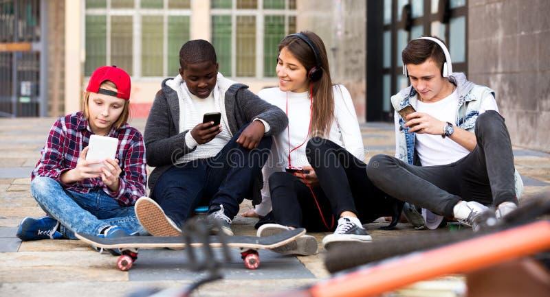 Adolescentes felizes que jogam em smarthphones fotografia de stock