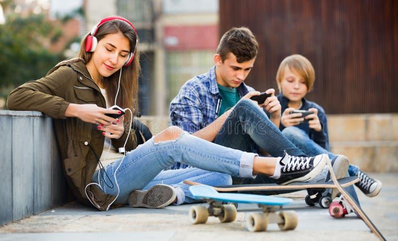 Adolescentes felizes que jogam em smarthphones e que escutam a música imagem de stock