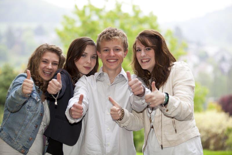 Adolescentes felizes que levantam os polegares acima fotografia de stock royalty free