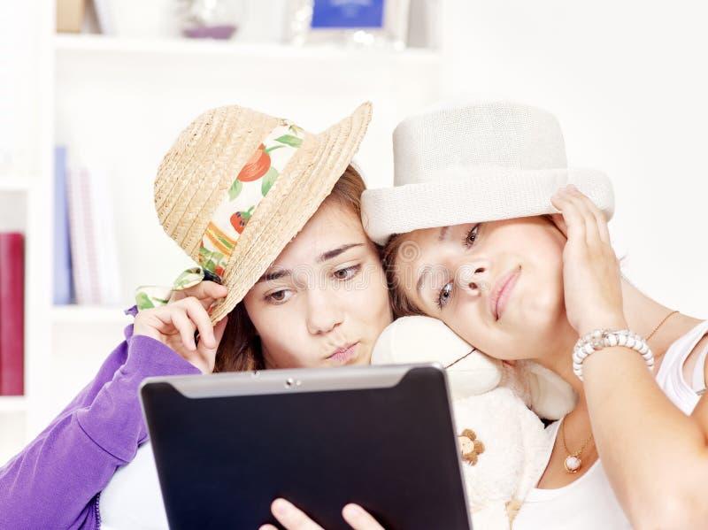 Adolescentes Felizes Que Têm O Divertimento Usando O Touchpad Imagem de Stock Royalty Free
