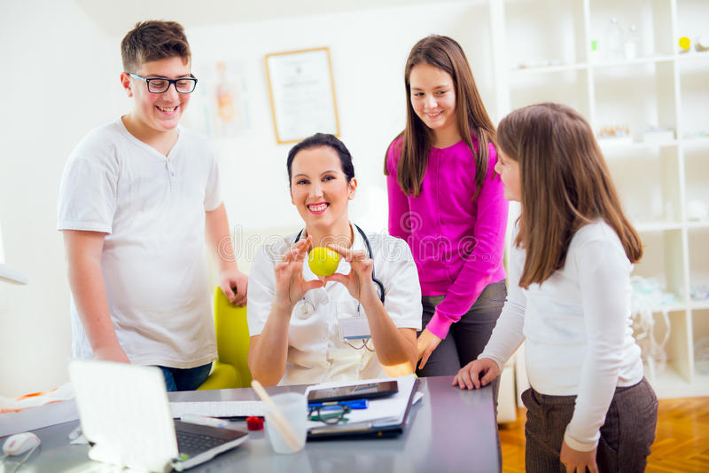 Adolescentes femeninos del nutricionista y del paciente del doctor Doctor que sostiene una manzana imagenes de archivo