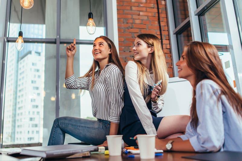 Adolescentes femeninos felices que se sientan en la tabla que mira y que señala las bombillas elegantes y que se relaja durante u fotos de archivo libres de regalías