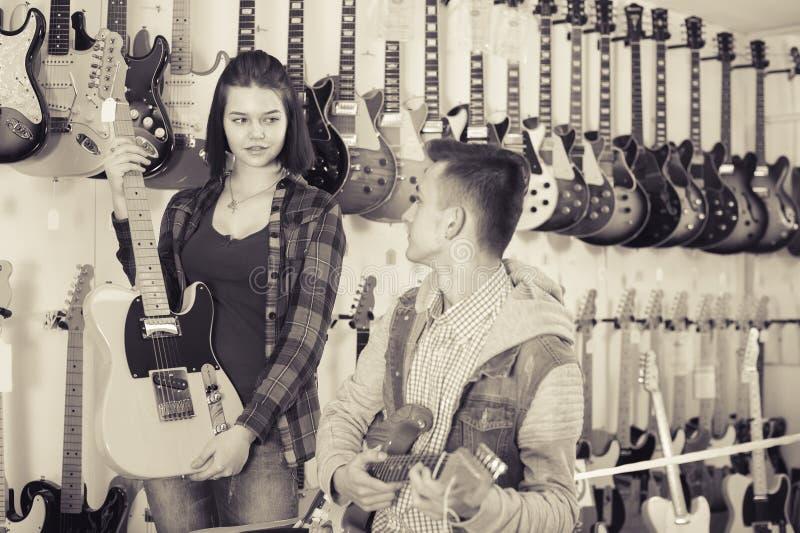 Adolescentes femeninos y masculinos atractivos que examinan las guitarras eléctricas fotografía de archivo libre de regalías