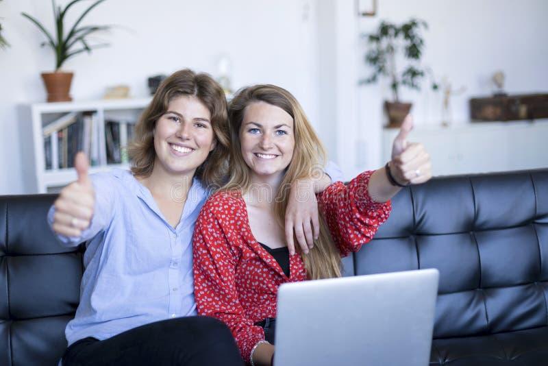 Adolescentes heureuses s'asseyant sur un sofa avec un ordinateur portable tout en montrant le pouce  photographie stock