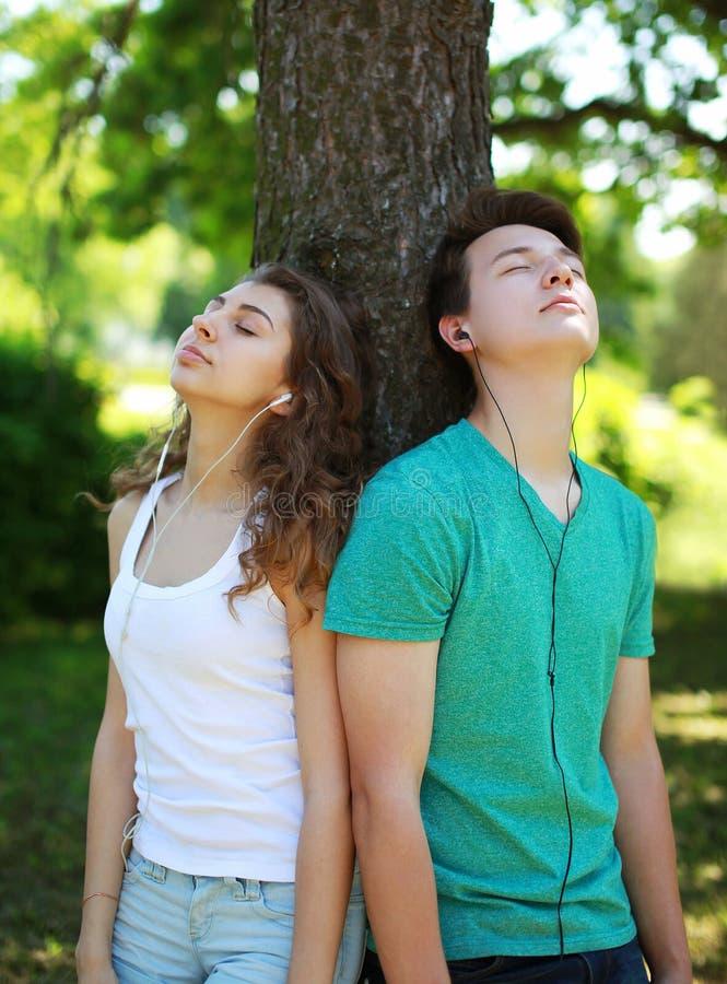 Adolescentes, indivíduo e menina nos fones de ouvido apreciando a escuta a música imagens de stock royalty free