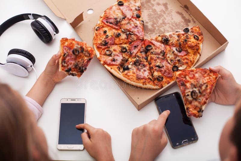 Adolescentes jovenes que comprueban sus teléfonos mientras que come la pizza imagenes de archivo