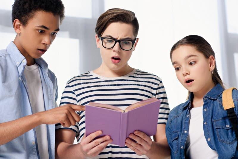 adolescentes multiculturais surpreendidos que olham o livro imagem de stock royalty free
