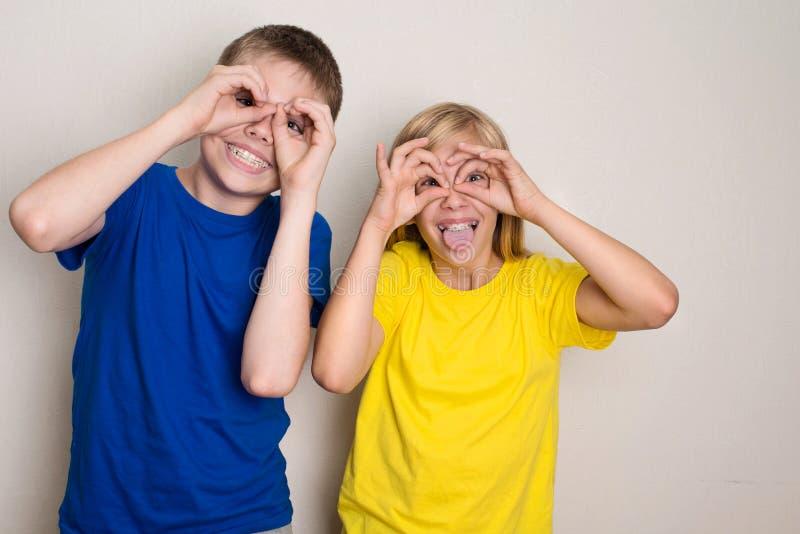 Adolescentes nas cintas dentais que têm o divertimento Menino e menina que fazem a careta engraçada das caras Saúde, amigos, adol fotos de stock