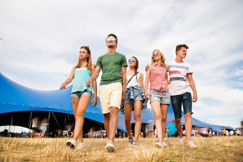 Adolescentes no festival de música do verão na frente da barraca azul grande imagem de stock royalty free