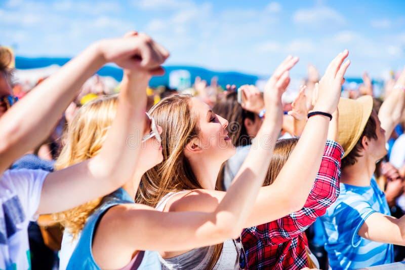 Adolescentes no festival de música do verão que tem o bom tempo imagens de stock royalty free