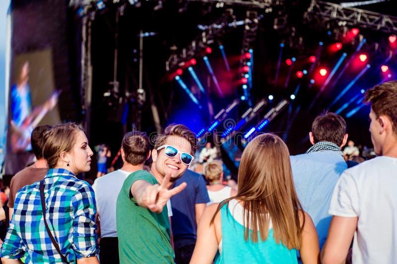 Adolescentes no festival de música do verão que tem o divertimento fotos de stock