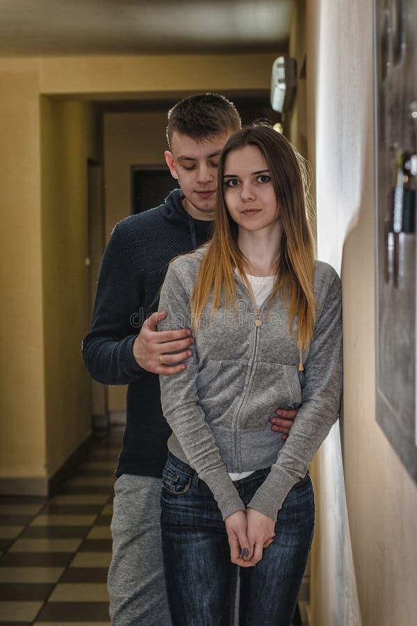 Adolescentes novio y novia que se abrazan en el pasillo de una construcción de viviendas imagen de archivo