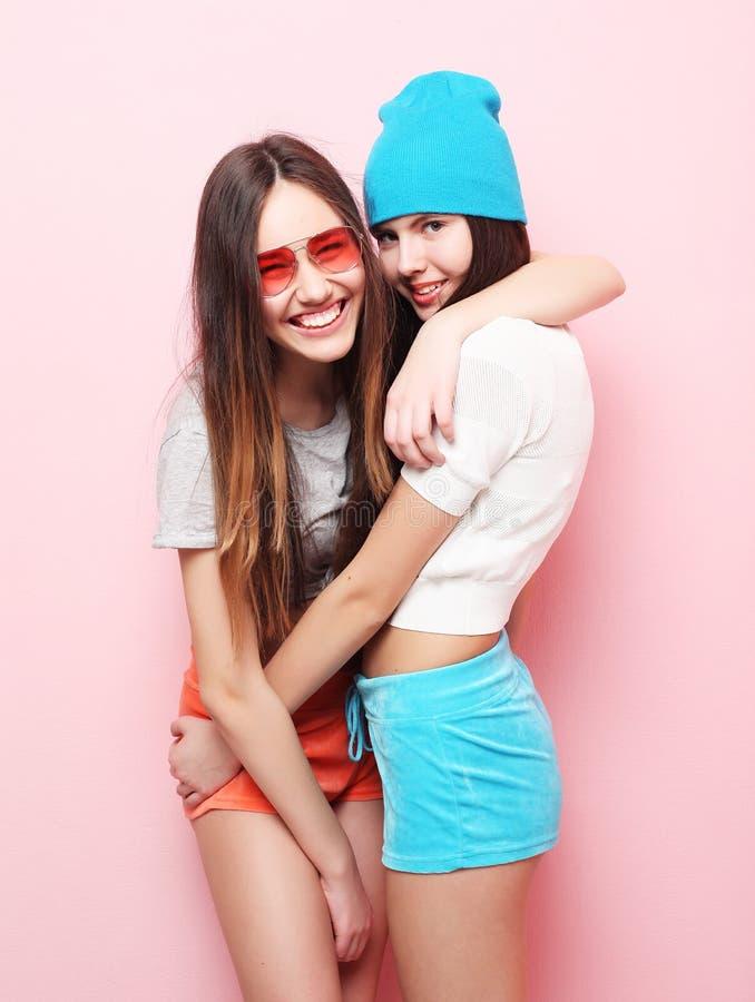 Adolescentes ou amigos bonitos de sorriso felizes que abraçam sobre o rosa fotos de stock