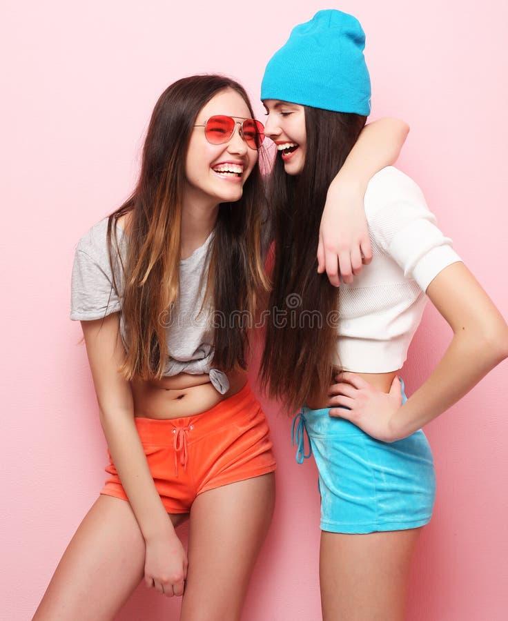 Adolescentes ou amigos bonitos de sorriso felizes que abraçam sobre o rosa fotografia de stock royalty free