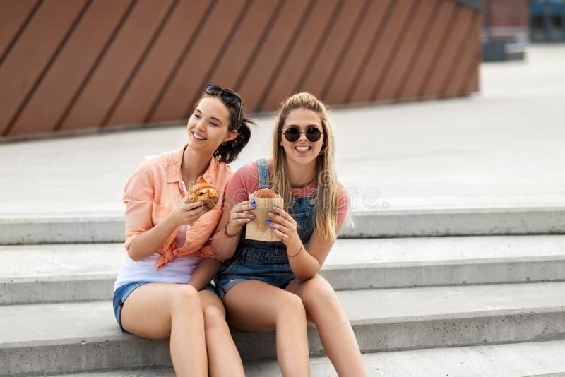 Adolescentes ou amigos que comem hamburgueres fora fotografia de stock