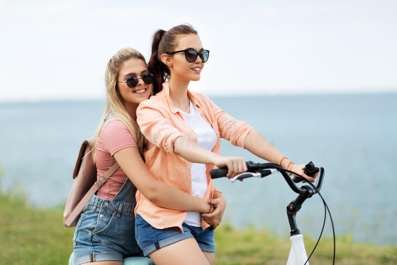 Adolescentes ou amigos que montam a bicicleta no verão foto de stock