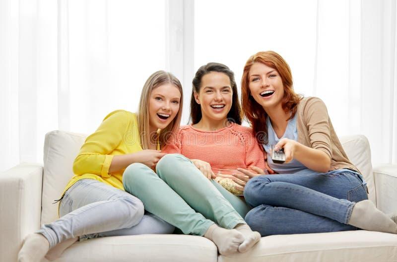 Adolescentes ou amis regardant la TV à la maison images stock