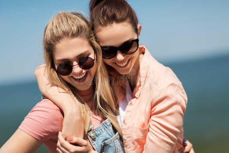 Adolescentes ou melhores amigos no beira-mar no verão imagens de stock