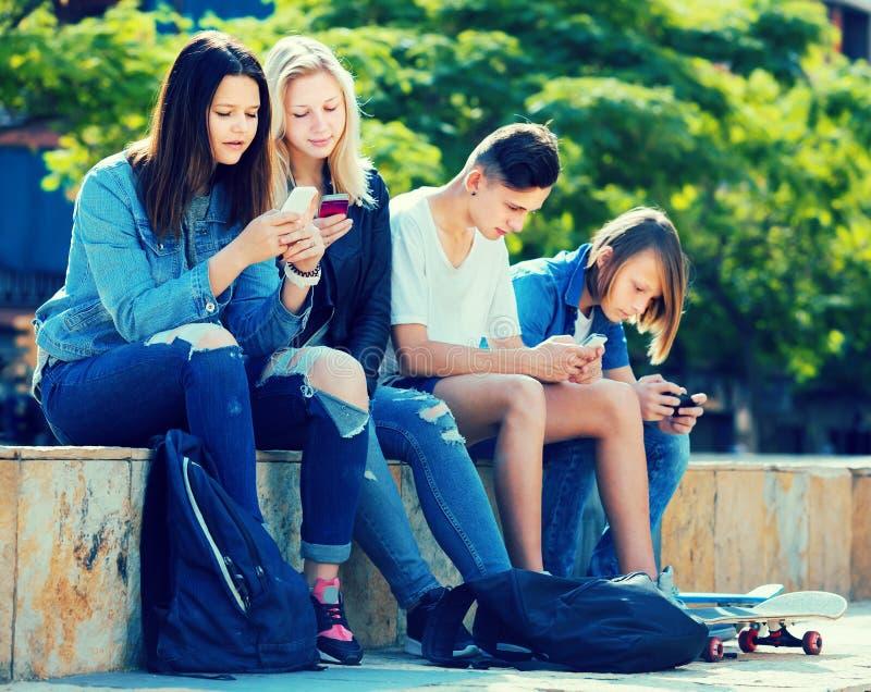 Adolescentes positivos que jogam com telefones celulares imagem de stock