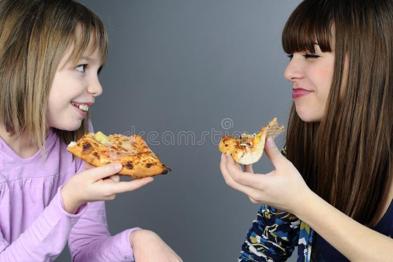 Adolescentes que comem e que têm o divertimento imagens de stock