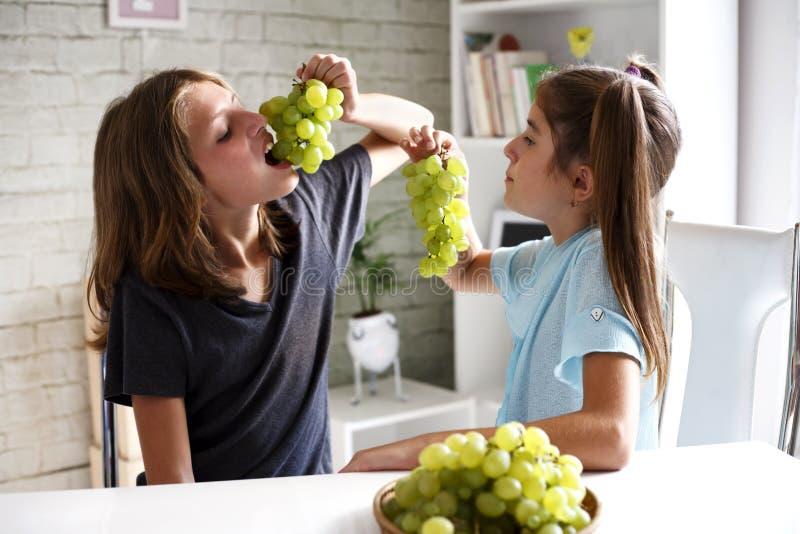 Adolescentes que comen las uvas fotos de archivo libres de regalías