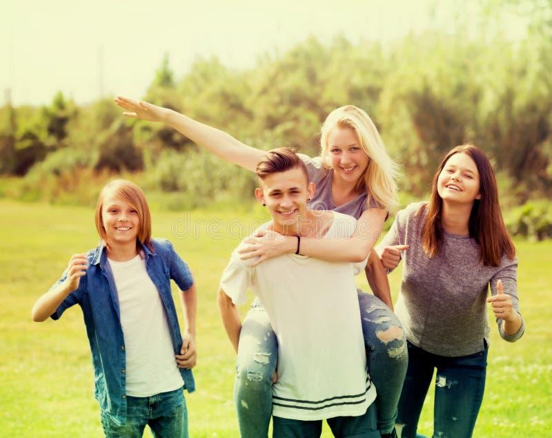 Adolescentes que corren en césped verde en parque imagenes de archivo