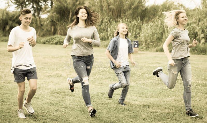 Adolescentes que corren a través de césped verde en verano en parque foto de archivo libre de regalías