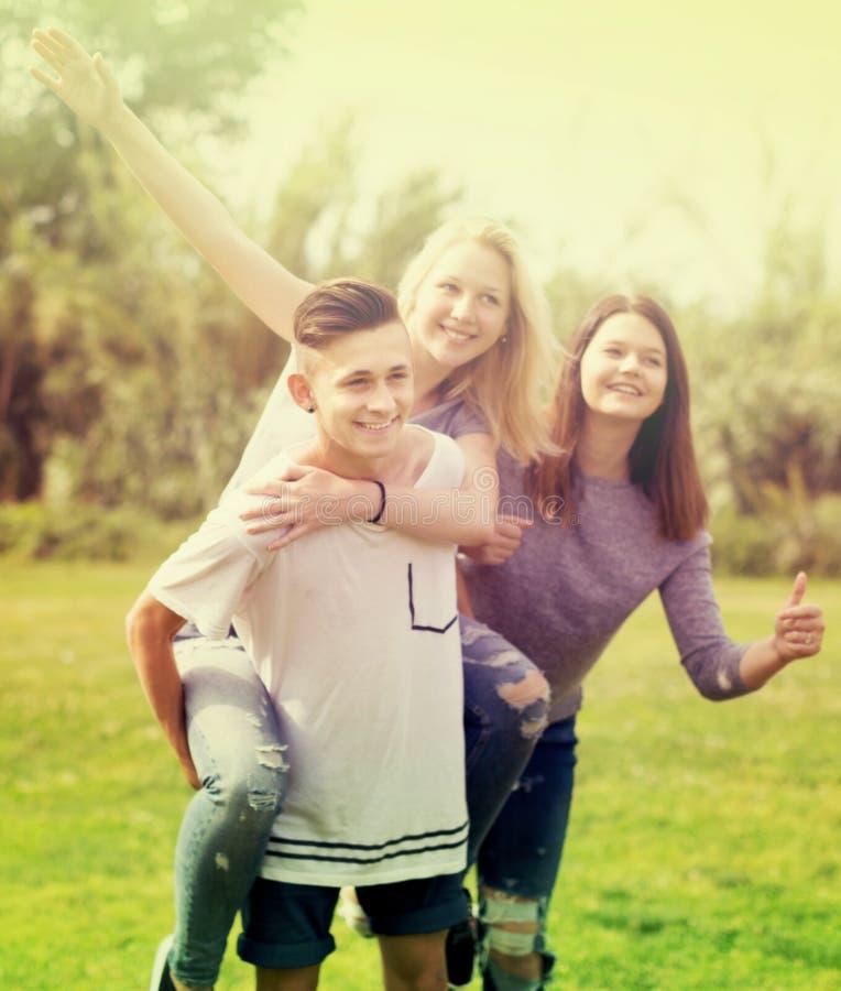 Adolescentes que corren a través de césped verde en verano en parque imagenes de archivo