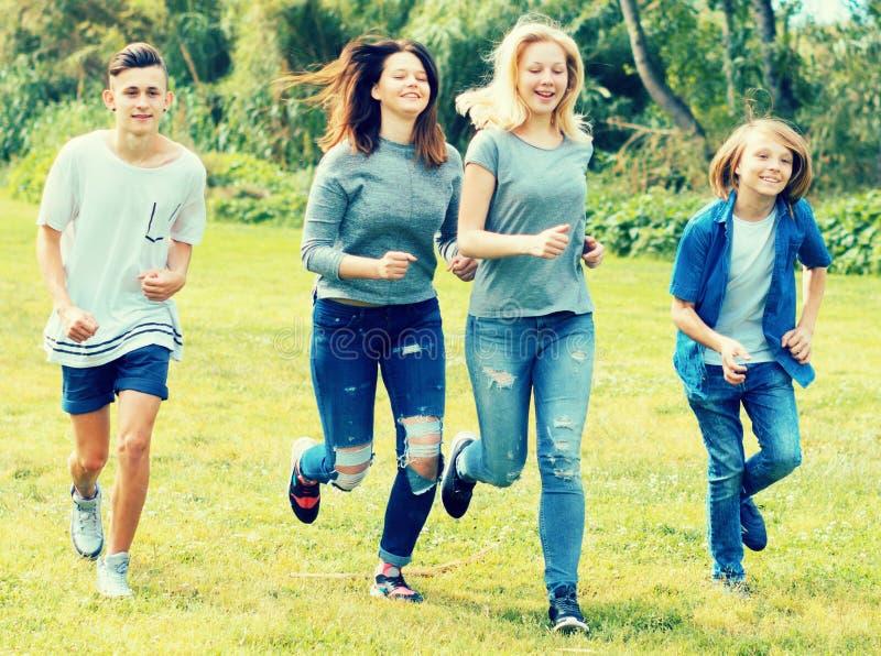 Adolescentes que corren a través de césped verde en verano en parque imágenes de archivo libres de regalías