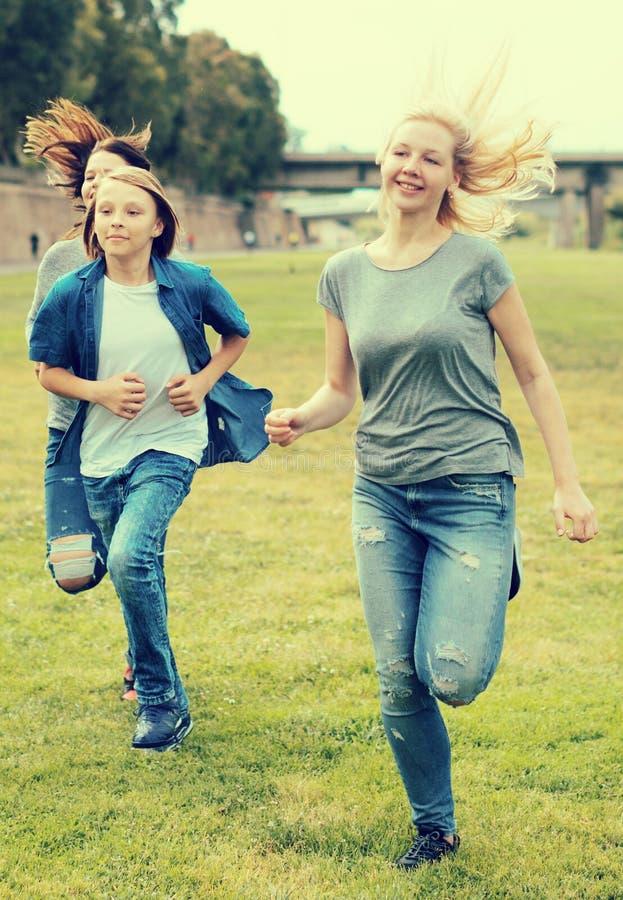 Adolescentes que corren a través de césped verde en verano en parque fotografía de archivo libre de regalías