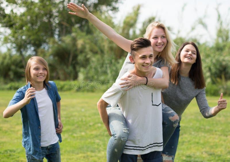Adolescentes que corren a través de césped verde en verano en parque imagen de archivo