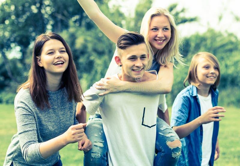 Adolescentes que corren a través de césped verde en verano en parque fotos de archivo