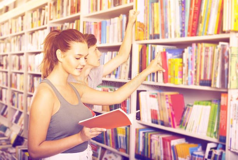 Adolescentes que guardam o livro e que leem a literatura nova foto de stock