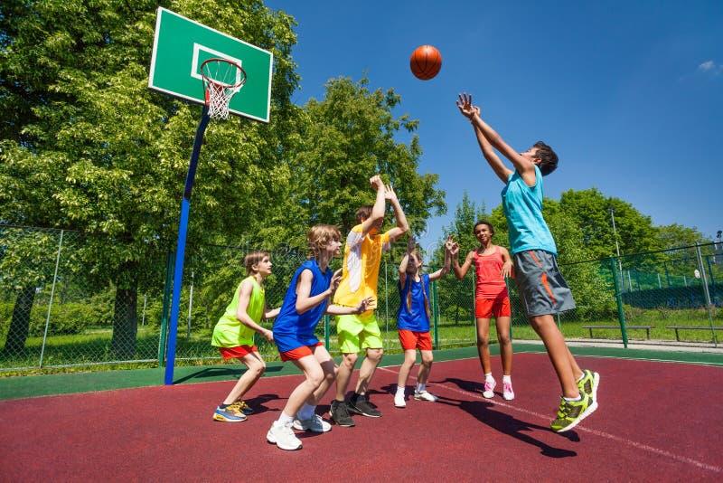 Adolescentes que jogam o jogo de basquetebol junto imagem de stock