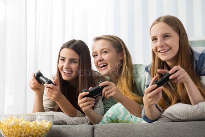 Adolescentes que jogam um jogo de vídeo fotografia de stock