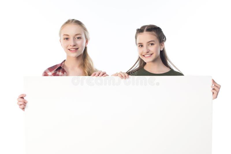 Adolescentes que mantêm a bandeira vazia isolada no branco imagem de stock royalty free