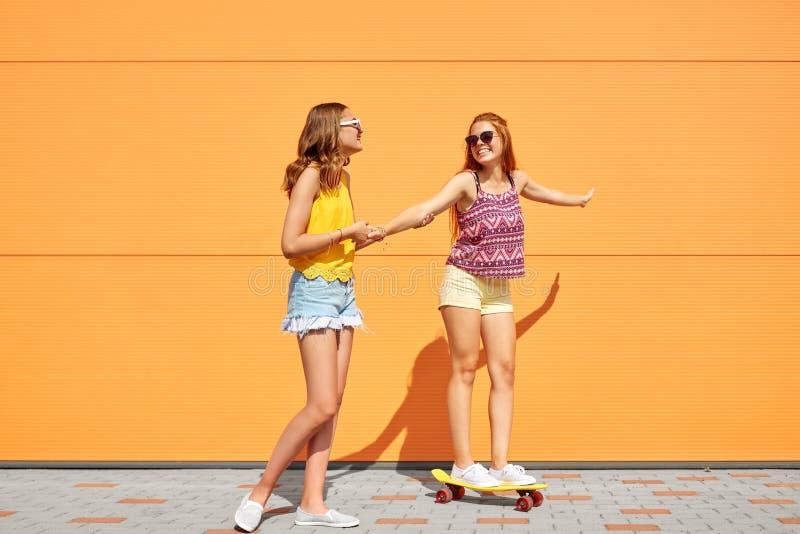 Adolescentes que montan el monopatín en la calle de la ciudad fotografía de archivo