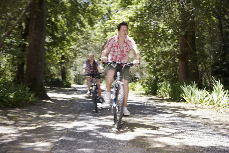 Adolescentes que montan en bicicleta en bosque fotografía de archivo
