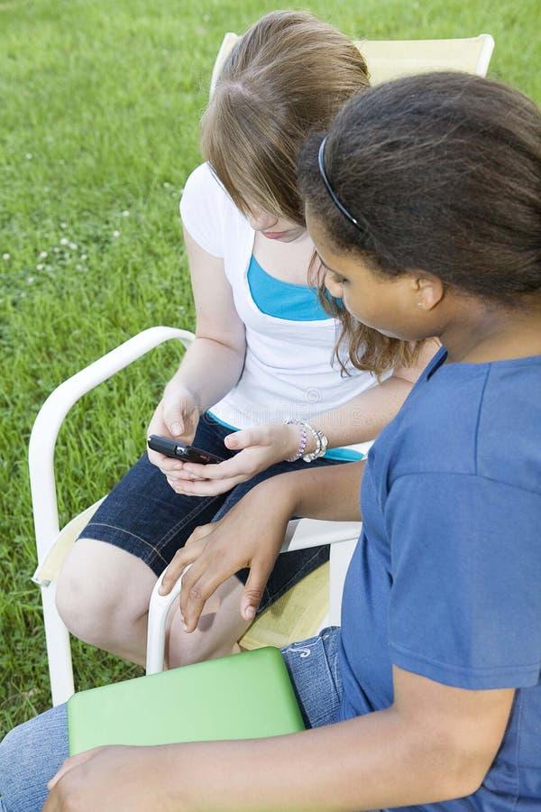 Adolescentes que olham o telefone de pilha imagens de stock royalty free
