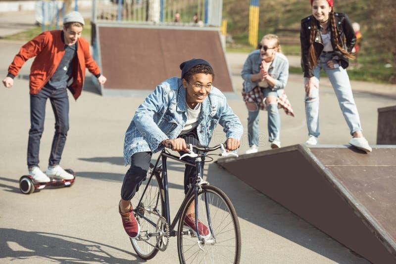 Adolescentes que passam o tempo no parque do skate, adolescentes que têm o conceito do divertimento foto de stock royalty free