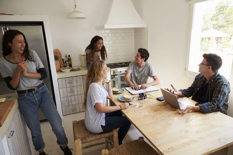 Adolescentes que penduram para fora na cozinha, fazendo trabalhos de casa e fazendo o alimento fotos de stock