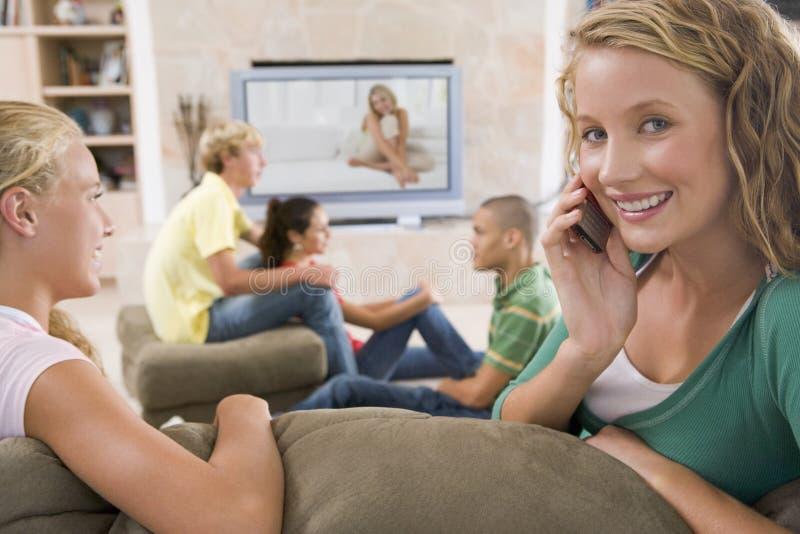 Adolescentes que penduram para fora na frente da televisão imagem de stock royalty free