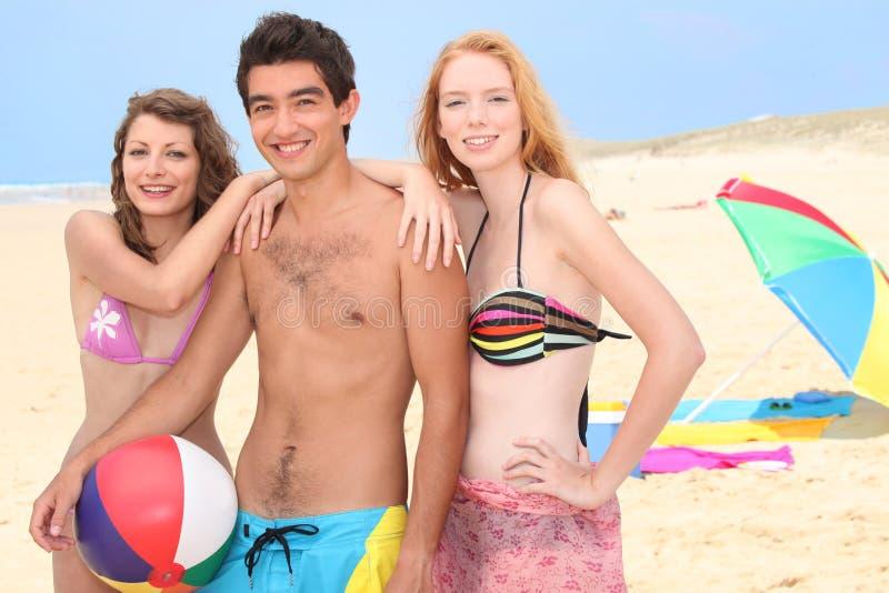 Adolescentes que penduram para fora na praia imagens de stock